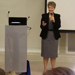 Brenda Bence speaking by podium